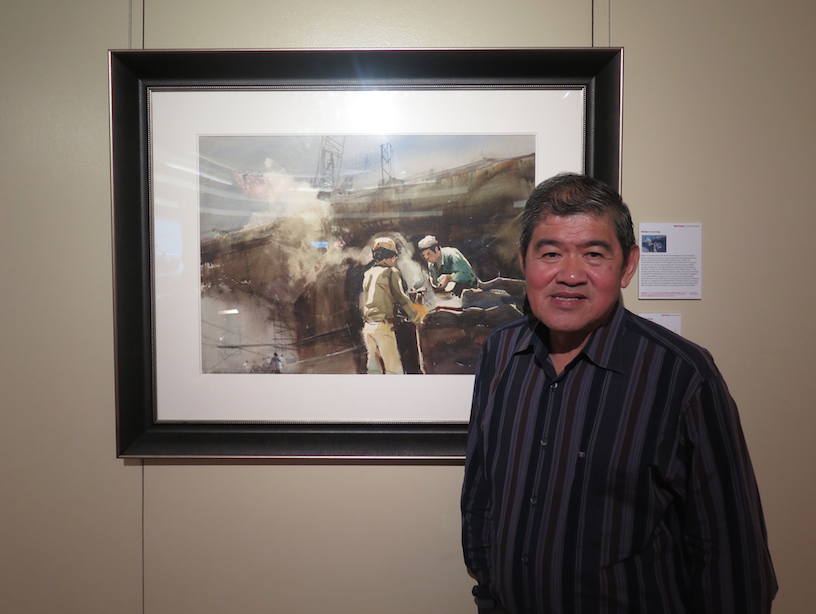 The humble Ong Kim Seng poses in front of his favourite painting, Welders in Jurong.